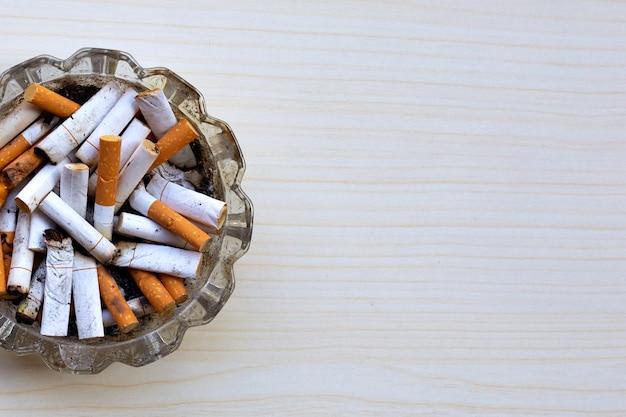 Mozziconi di sigaretta nel posacenere di vetro