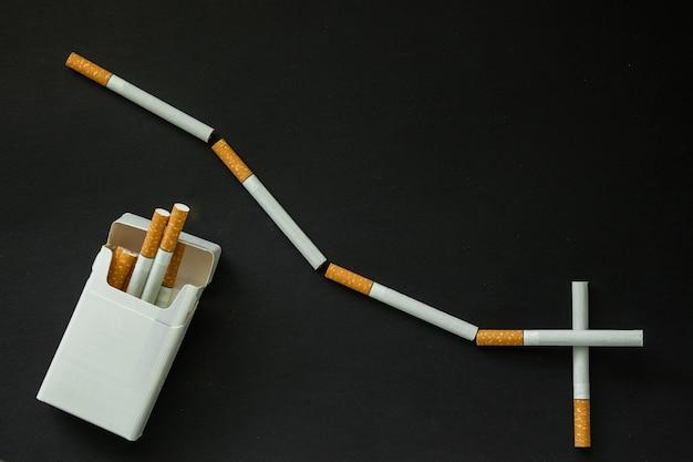 Sigaretta su una superficie scura. portacenere. smettere di fumare
