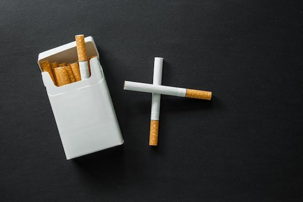 Sigaretta su una superficie scura. portacenere. smettere di fumare Foto Premium