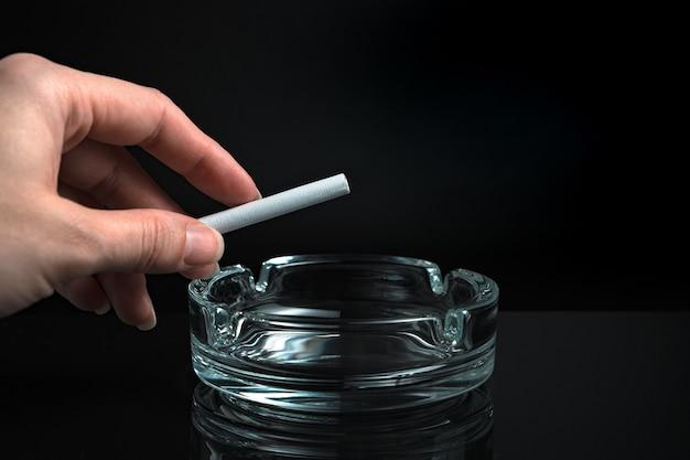 Sigaretta in mano su un portacenere su sfondo nero.
