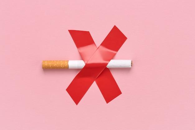 Una sigaretta è barrata con una croce, un cartello rosso vietato fumare.