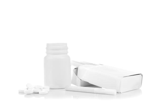 Sigaretta, confezione e pillole isolate su bianco