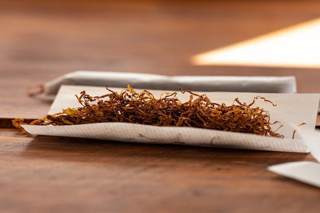 Carta per sigarette e mucchio di tabacco sul tavolo di legno