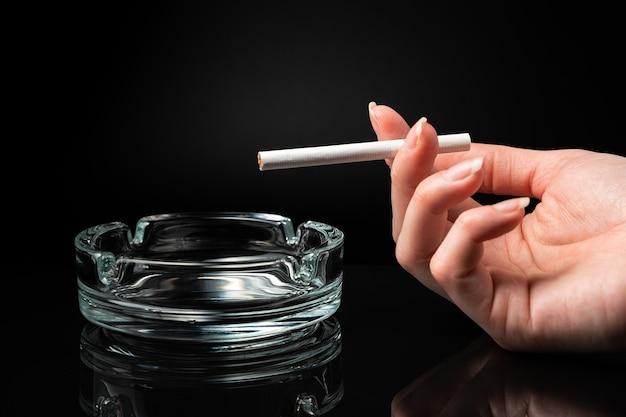 Una sigaretta in mano a una donna accanto a un portacenere su sfondo nero.