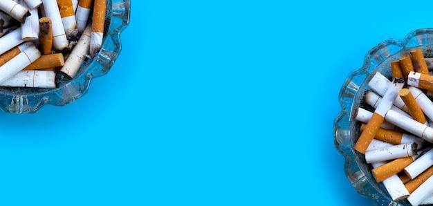 Germogli di sigarette sulla superficie blu