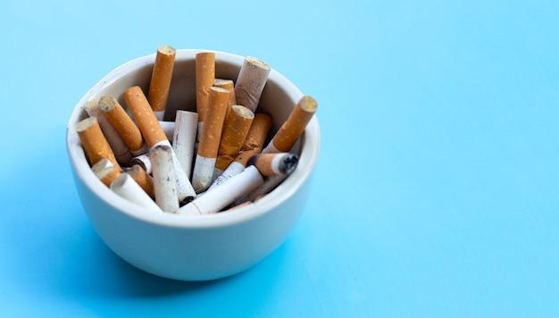 Boccioli di sigarette in un portacenere trasparente sullo spazio blu. copia spazio