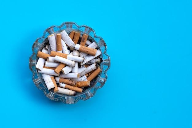 Boccioli di sigarette in un portacenere trasparente sull'azzurro.