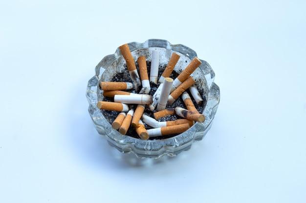 Boccioli di sigarette in un portacenere trasparente su bianco.