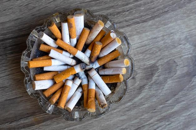 Boccioli di sigarette in un portacenere trasparente su uno spazio di legno. copia spazio
