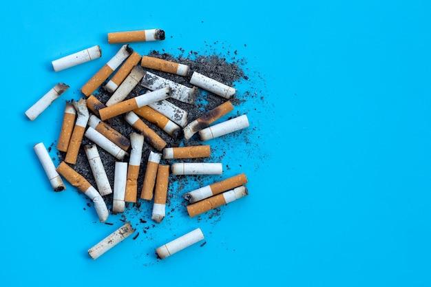 Boccioli di sigarette con posacenere sulla superficie blu