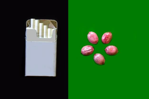 Sigarette su sfondo scuro e caramelle su sfondo verde rinunciando alle sigarette a favore delle caramelle