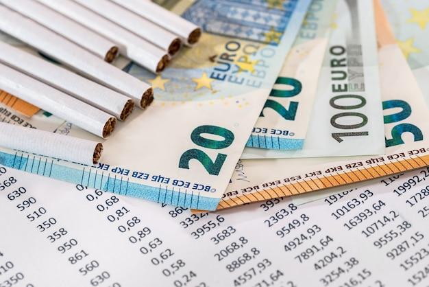 Sigarette con banconote in euro sull'estratto conto bancario