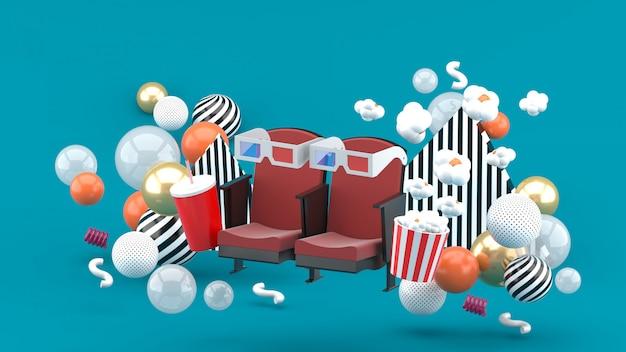 Sedia da cinema bevande analcoliche e popcorn tra le palline colorate sul blu. rendering 3d.