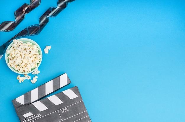 Concetto di cinema - ciak con popcorn e striscia di pellicola su sfondo blu con spazio di copia.
