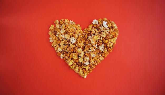 Concetto di amanti del cinema di popcorn. popcorn lanuginoso bianco a forma di cuore sulla parete rossa. san valentino