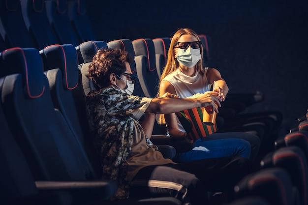 Cinema, cinema durante la quarantena. regole di sicurezza per la pandemia di coronavirus, distanza sociale durante la visione di film. uomini e donne che indossano una maschera protettiva seduti in una fila di auditorium, mangiando po