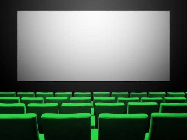 Cinema cinema con sedili di velluto verde e uno schermo bianco vuoto