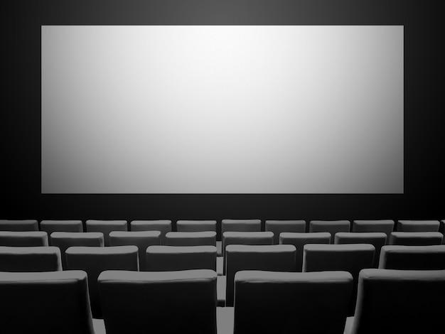 Cinema cinema con sedili in velluto e uno schermo bianco vuoto
