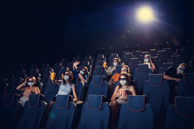 Cinema in quarantena. regole di sicurezza per la pandemia di coronavirus, distanza sociale durante la visione di film. uomini, donne in maschera protettiva seduti in una fila di auditorium. tempo libero, concetto di cultura giovanile.