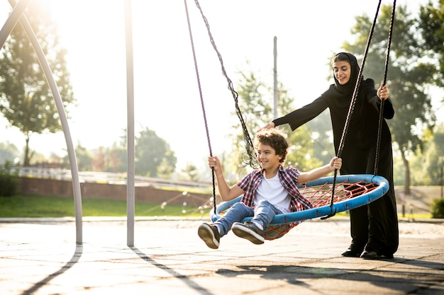 Immagine cinematografica di una donna degli emirati con i suoi bambini che si divertono al parco giochi