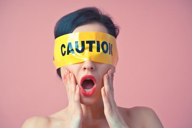 Cinematica una donna con un nastro giallo sul viso. concetto di arte astratta