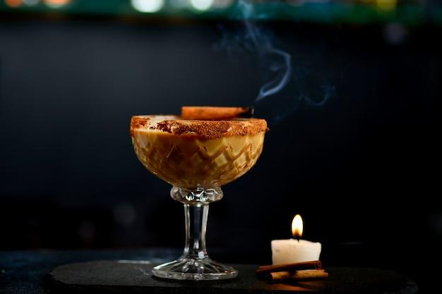 Bevande alcoliche alla cannella, aperitivo con cannella di fumo e candela su un bar scuro
