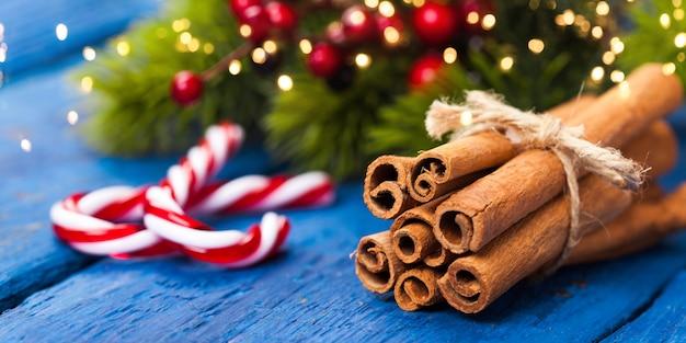 Cannella e caramelle con decorazioni natalizie sulla tavola di legno blu