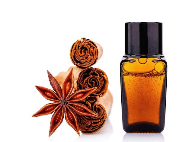 Bottiglia di olio essenziale di cannella con bastoncini di cannella di ceylon e anice stellato isolato su bianco.