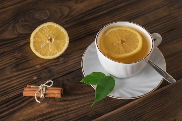 Cannella e limone e una tazza di tè su un tavolo di legno. una bevanda tonificante utile per la salute.