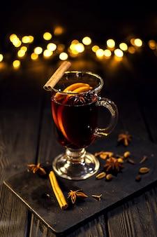 La cannella si trova in un bicchiere, primo piano bicchiere di vin brulé con arancia e cannella su nero scuro, albero di natale e luci, grande bokeh giallo, set di vin brulè