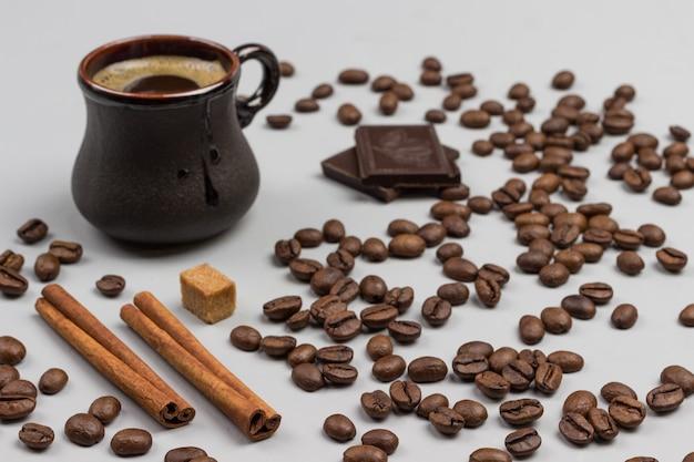 Bastoncini di cannella e chicchi di caffè, cioccolato e panini alla cannella su sfondo bianco