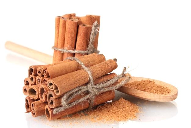 Bastoncini di cannella e polvere in cucchiaio di legno isolato su bianco