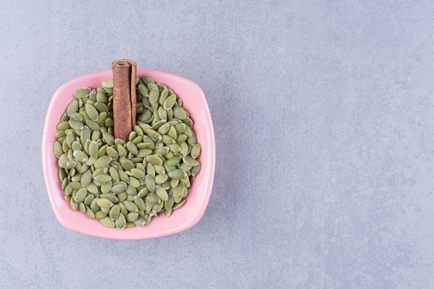 Bastoncini di cannella e semi di zucca in una ciotola sulla superficie di marmo