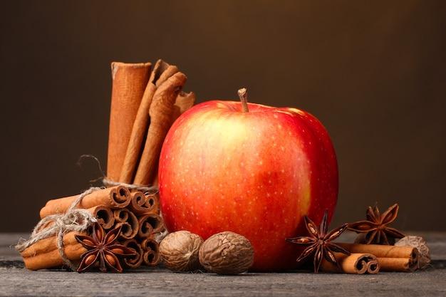 Bastoncini di cannella, mela rossa, noce moscata e anice sul tavolo di legno