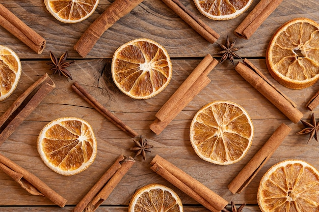 Bastoncini di cannella, fette di arancia essiccata, anice stellato su fondo di legno. vista dall'alto. concetto di celebrazione di natale e capodanno. sfondo del modello.