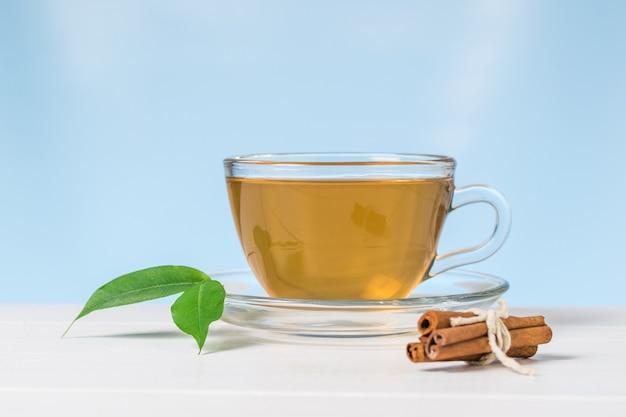 Bastoncini di cannella e tè con foglie verdi su un tavolo bianco su sfondo blu. una bevanda tonificante utile per la salute.