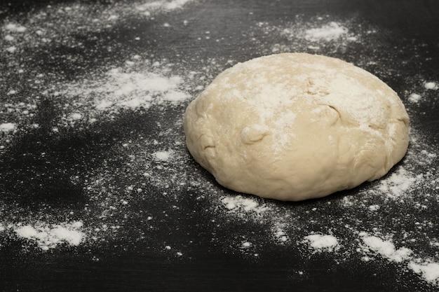 Cerchio di pasta su uno sfondo nero nella farina
