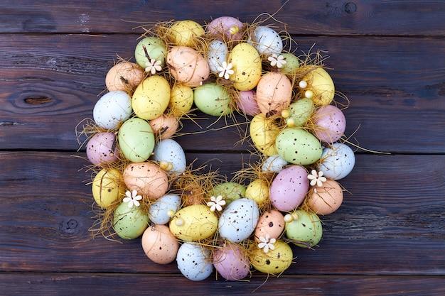 Cerchio fatto di uova di pasqua multicolori. raccolta delle uova di pasqua su un tavolo in legno rustico scuro.