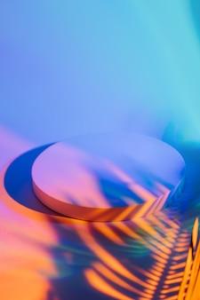 Podio circolare con ombra di una foglia di palma su uno sfondo luminoso ed elegante a colori per mostrare i prodotti.