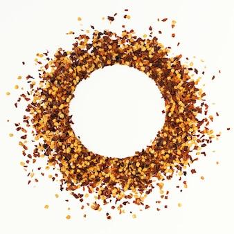 Cornice a forma di cerchio di pepe di cayenna rosso tritato, fiocchi di peperoncino essiccato e semi isolati su sfondo bianco