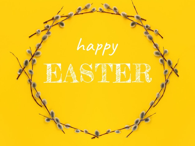 Corona del cerchio con un ramo di salice con gemme e testo buona pasqua su un giallo. vacanza primaverile e simbolo della domenica delle palme ad aprile.