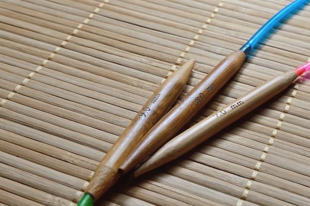 Ferri da maglia di bambù circolari su una superficie di legno.