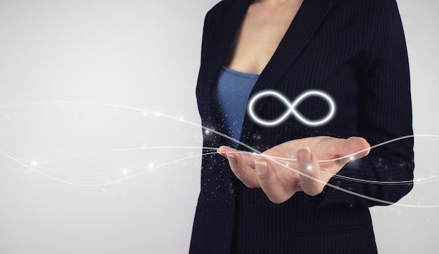 Economia circolare con concetto infinito. tenere in mano il simbolo infinito dell'ologramma digitale su sfondo grigio. il concetto di internet illimitato, risorse materiali rinnovabili.