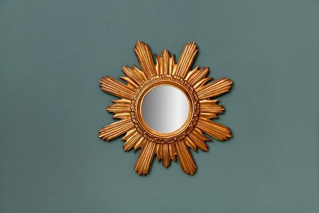 Specchio circolare con cornice vintage dorata con motivo a stella, appeso a una parete color ottanio