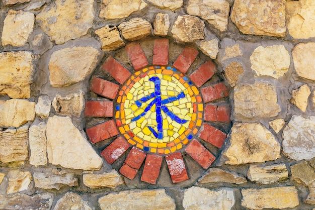 Simbolo religioso del mosaico circolare del confucianesimo sul muro di pietra.