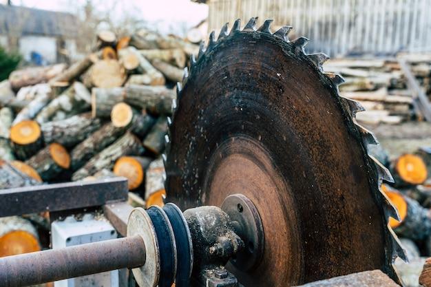 Sega circolare con mucchio di tronchi di ontano in background con spazio di copia, concetto di duro lavoro