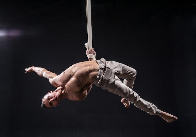 Artista di circo sulle cinghie aeree con muscoli forti sul nero