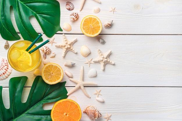 Bevanda rinfrescante agli agrumi sullo sfondo di conchiglie e foglie tropicali
