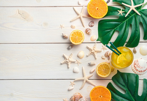 Bevanda rinfrescante agli agrumi e conchiglie e foglie tropicali su fondo di legno bianco
