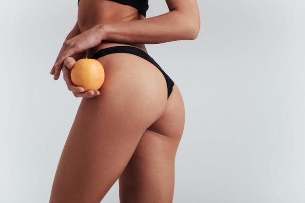 Dieta degli agrumi. foto di particelle di ragazza in biancheria intima nera in piedi al muro bianco e tenendo l'arancia.